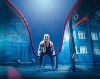 La mujer con batalla de la cuerda de la batalla ropes ejercicio en el gimnasio de la aptitud fotos de archivo