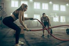 La mujer con batalla ropes ejercicio en el gimnasio de la aptitud imagen de archivo