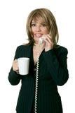 La mujer con café contesta a un teléfono fotos de archivo libres de regalías