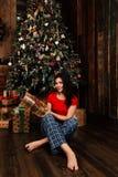 La mujer con la caja del regalo de Navidad en fondo adornó el árbol de navidad Morenita en una camisa roja Foto de archivo