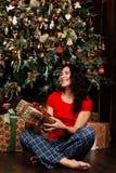 La mujer con la caja del regalo de Navidad en fondo adornó el árbol de navidad Morenita en una camisa roja Fotos de archivo libres de regalías