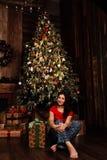 La mujer con la caja del regalo de Navidad en fondo adornó el árbol de navidad Morenita en una camisa roja Fotografía de archivo