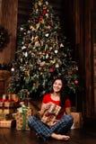 La mujer con la caja del regalo de Navidad en fondo adornó el árbol de navidad Morenita en una camisa roja Fotografía de archivo libre de regalías