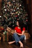 La mujer con la caja del regalo de Navidad en fondo adornó el árbol de navidad Morenita en una camisa roja Imagenes de archivo