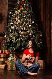 La mujer con la caja del regalo de Navidad en fondo adornó el árbol de navidad Morenita en una camisa roja Imágenes de archivo libres de regalías