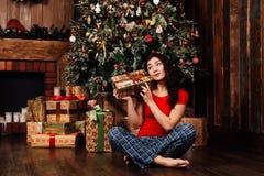 La mujer con la caja del regalo de Navidad en fondo adornó el árbol de navidad Morenita en una camisa roja Foto de archivo libre de regalías