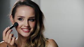La mujer con la cara de la belleza que aplica maquillaje se ruboriza con el cepillo almacen de metraje de vídeo