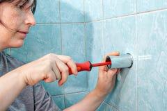 La mujer con destornillador, aprieta el soporte del tornillo para la ducha para emparedar foto de archivo libre de regalías