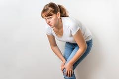 La mujer con dolor de la rodilla está llevando a cabo su pierna de dolor Fotos de archivo libres de regalías