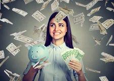 La mujer con efectivo de la hucha y del euro debajo del dinero del dólar llueve Imágenes de archivo libres de regalías