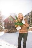 La mujer con el árbol de navidad que muestra los pulgares sube cerca de casa de la montaña Imagen de archivo