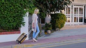 La mujer con el bolso del viaje en las ruedas viene a la puerta del hotel Llegada en el hotel o de vacaciones almacen de video