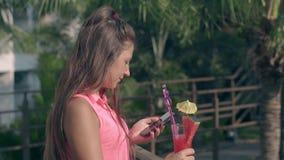 La mujer con el cóctel de la baya a disposición se coloca en territorio del hotel metrajes
