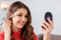 La mujer con el cepillo y el espejo de la sombra de ojos hace maquillaje Fotos de archivo libres de regalías