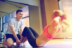 La mujer con el instructor personal que el hacer se sienta sube en gimnasio imágenes de archivo libres de regalías