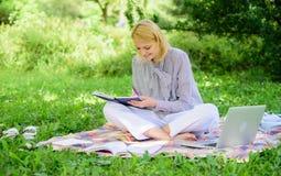 La mujer con el ordenador portátil se sienta en prado de la hierba de la manta La muchacha con la libreta escribe la nota Concept fotografía de archivo