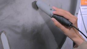 La mujer con el palillo del imán controla partículas del ironsand almacen de video
