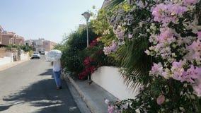 La mujer con el paraguas decorativo camina en la calle almacen de metraje de vídeo