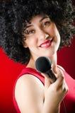 La mujer con el peinado afro que canta en Karaoke imágenes de archivo libres de regalías