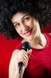 La mujer con el peinado afro que canta en Karaoke imagenes de archivo
