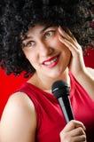 La mujer con el peinado afro que canta en Karaoke fotografía de archivo