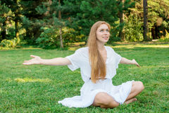 La mujer con el pelo largo enganchó a yoga en la naturaleza Foto de archivo