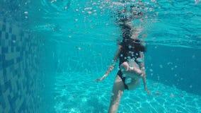 La mujer con el pelo largo se zambulle en la piscina metrajes