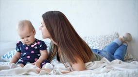 La mujer con el pelo oscuro largo está besando a su hija pequeña, mintiendo en un dormitorio almacen de video