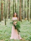 La mujer con el pelo rizado largo en el vestido rosa claro largo está sosteniendo el ramo enorme de flores rojas, blancas y de ve Imágenes de archivo libres de regalías