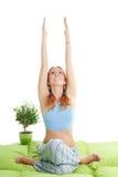 La mujer con el pelo rojo hace ejercicios de la yoga Foto de archivo