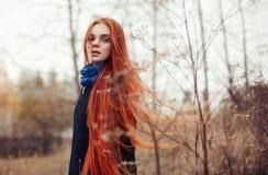 La mujer con el pelo rojo largo camina en otoño en la calle Mirada soñadora misteriosa y la imagen de la muchacha El caminar de l fotos de archivo