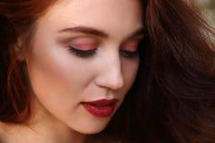 La mujer con el pelo rojo sonríe y mira abajo Foto de archivo libre de regalías