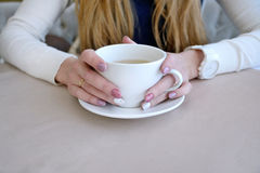 La mujer con el pelo rubio da sostener la taza blanca Foto de archivo libre de regalías
