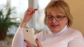La mujer con el smartphone blanco habla la sonrisa, ríe y gesticula almacen de metraje de vídeo