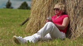 La mujer con el smartphone blanco se sienta cerca de pajar y escucha la música metrajes