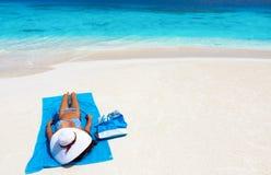 La mujer con el sunhat se relaja en una playa tropical imagen de archivo libre de regalías
