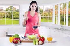 La mujer con el superfood muestra el pulgar para arriba Imagen de archivo