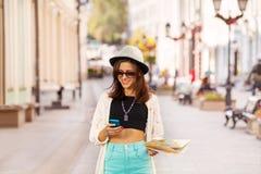 La mujer con el teléfono móvil y la ciudad trazan en la calle Imagen de archivo libre de regalías