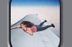 La mujer con el teléfono miente en el ala plana en vuelo Fotos de archivo libres de regalías