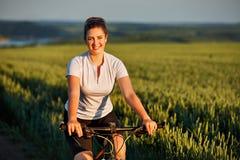 La mujer con la bici disfruta de vacaciones de verano en el prado hermoso Fotos de archivo libres de regalías