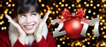 La mujer con la bola roja de la Navidad, sonriendo y mira para arriba en luces Fotos de archivo libres de regalías
