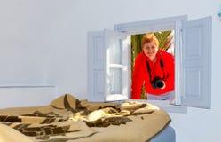 La mujer con la cámara en la ventana de la casa Foto de archivo