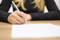 La mujer con la camisa negra está firmando el documento jurídico fotografía de archivo libre de regalías