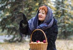 La mujer con la cesta de manzanas en el bosque, viene la primera nieve fotos de archivo