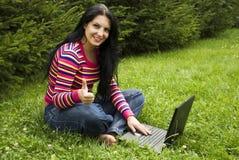 La mujer con la computadora portátil en naturaleza da los pulgares para arriba Imágenes de archivo libres de regalías
