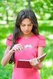 La mujer con la lupa sostiene el libro Foto de archivo