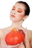 La mujer con la naranja compone la calabaza de la explotación agrícola Fotos de archivo
