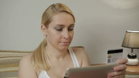 La mujer con la tableta hace un pago por la tarjeta de crédito en casa almacen de metraje de vídeo
