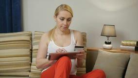 La mujer con la tableta hace un pago por la tarjeta de crédito en casa almacen de video