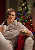 La mujer con la taza de bebida consigue aburrida mirando la TV Imagen de archivo